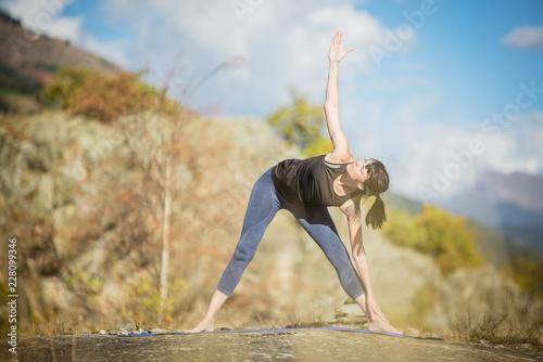 Fototapeta Yoga nel parco. Giovane ragazza pratica yoga all'aperto.