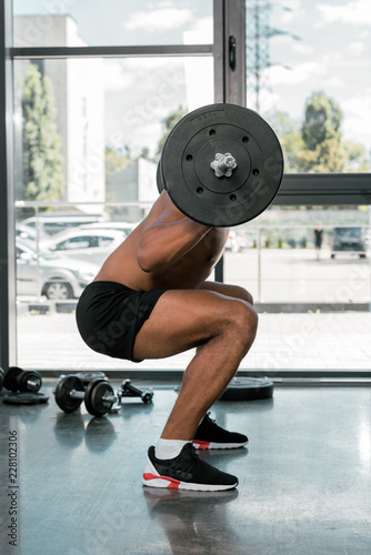 Poster side view of young athletic man lifting barbell in gym
