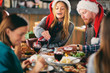 Friends having dinner at home at Christmas eve. Winter holidays concept. - 228102743
