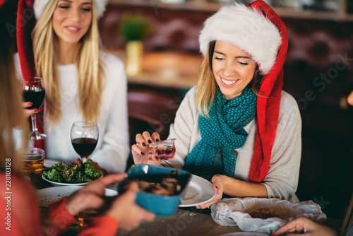Friends having dinner at home at Christmas eve. Winter holidays concept. - 228103128