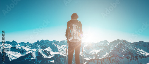 Hiker standing against sun in winter mountains