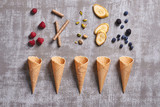 Top view of pistachios,banana slices,chocolate sticks,raspberries, blueberries falling in waffle cones on a grey background