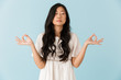 Beautiful woman isolated over blue background meditate.