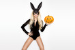 Beautiful young blonde woman holding pumpkin for Halloween
