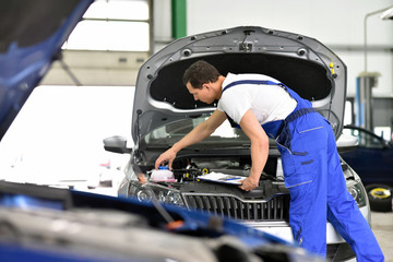 car mechanic in a workshop - engine repair and diagnosis on a vehicle