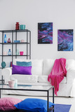 Pink blanket on white sofa in cosmos living room interior with table and posters with stars. Real photo