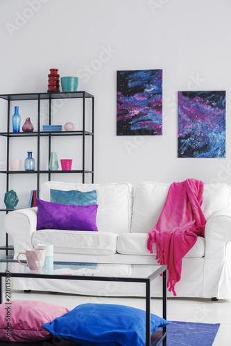 Pink blanket on white sofa in cosmos living room interior with table and posters with stars. Real photo - 228135107