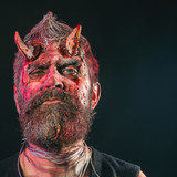 Halloween demon with bloody horns on head - 228137740
