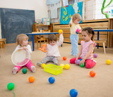 Group of children playing balls in kindergarten or daycare centre - 228140592
