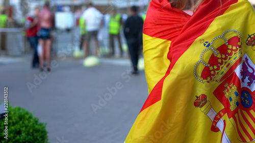 Leinwanddruck Bild Female covered with Spanish flag standing in street, country patriot at rally