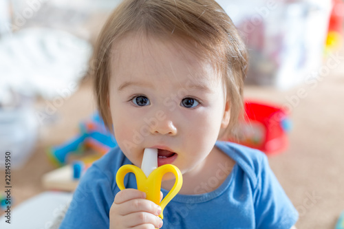 Toddler boy with a teething toy in his house
