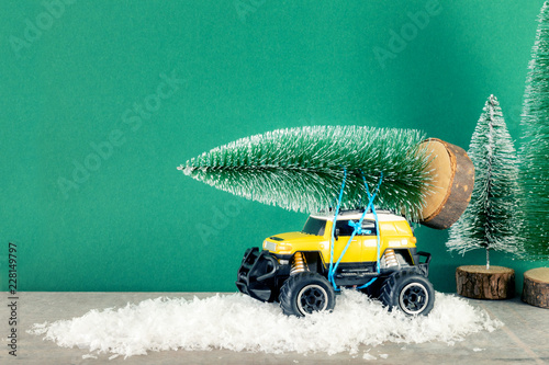 Foto Murales yellow SUV monster car truck toy with fir tree