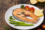 Salmon Grilled on a white plate on wooden table - 228149999