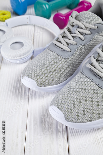 Foto Murales Gray sport shoes, white earphones, colored dumbbells and measuring tape on wooden table