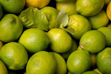 Pile of fresh green yellow limes at market for sale - top view