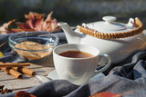 tea in a white cup, a teapot, brown sugar and spices on a wooden table with grey cloth, tea time in autumn - 228157999