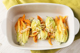 stuffed zucchini or courgette blossoms in a casserole dish on a green napkin, cooking a mediterranian appetizer, high angle view from above - 228158520