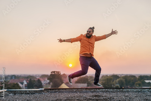 Picture of happy cheerful modern young man on roof top dancing and celebrating success and good news.