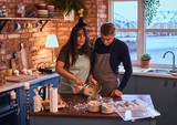 Attractive couple with makeup together cooking breakfast in loft style kitchen at morning. - 228172906