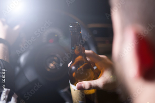 Drunk young man driving a car with a bottle of beer. Don't drink and drive concept. Driving under the influence. DUI, Driving while intoxicated. DWI