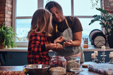 Happy mom cooking with her little daughter in loft style kitchen at morning. - 228174556