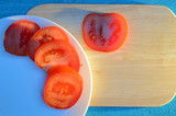 tomato slices are laid out on a wooden cutting board and white ceramic plate with a blue-turquoise table illuminated by the sun with long cold shadows