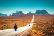 Leinwandbild Motiv Biker on Monument Valley road at sunset, USA
