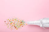 Champagne bottle with colorful sprinkles on pink background - 228179556