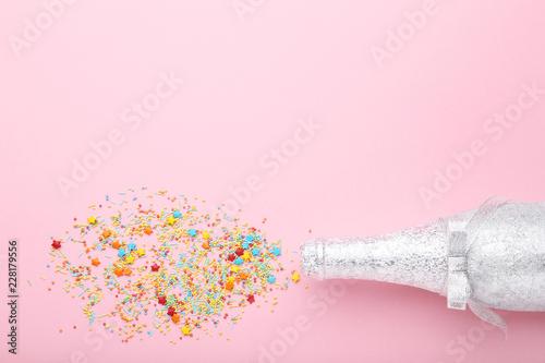 Szampańska butelka z kolorowym kropi na różowym tle