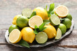 Leinwanddruck Bild - Lemons and limes with green leafs on grey wooden table
