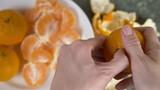 women's hands peel the peel of mandarins, mandarin slices are piled in a bowl.