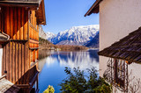 Snow covered Alps on the background of spectacular view from old wooden house on the mountain lake