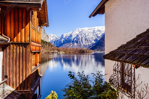 Poster Snow covered Alps on the background of spectacular view from old wooden house on the mountain lake