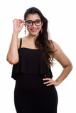 Young happy Indian woman smiling while holding eyeglasses