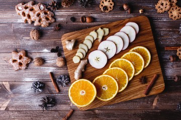 Mulled wine cooking. Oranges, apples and species lie on wooden table readyfor mulled wine