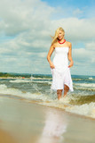 Blonde woman wearing dress walking in water - 228212770