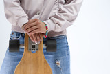 Closeup of hands of Caucasian Girl in Pink Hoodie Holding Longboard In Front. Against White. - 228214927