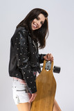 Lifestyle Concepts. Portrait of Positive Caucasian Brunette Girl In Black Leather Jacket Posing With Longboard. Against White. - 228215122