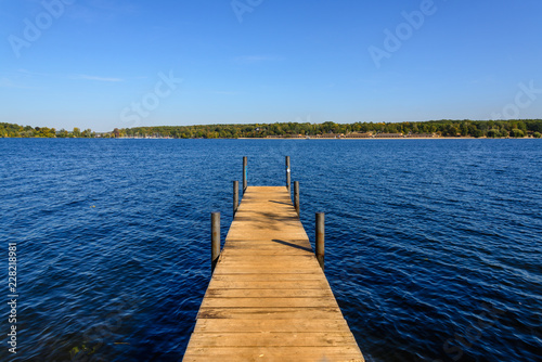Acrylglas Pier View from long wooden pier onto Wannsee lake and Havel river during sunny day, clear sky in autumn in Berlin, Germany.