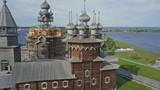 Aerial shot of Kizhi Island main church under renovation with green lawn, farm, authentic old architecture, UNESCO - 228223984