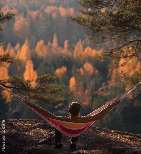 Foto Murales A man sits in a hammock and admires the autumn forest. View from the back.