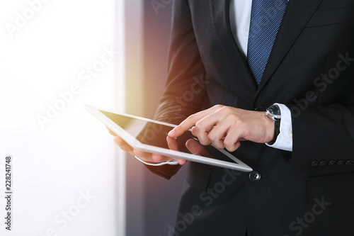 Poster Unknown businessman holding digital tablet in office