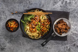 Chinese noodles with mushrooms, fried meat in a pan, vegetables and herbs are on the gray table. Top view