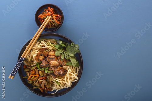 Traditional Chinese noodles noodles with fried meat and salad in a porcelain plate on a blue table. Copy space. Top view