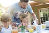 Family having breakfast in summer morning - 228253334