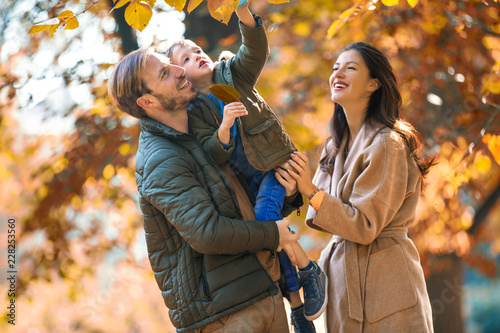 Young family having fun in the autumn park with his son.