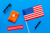 Immigration to United States of America concept. Textimmigration near passport cover and USA flag on blue background top view