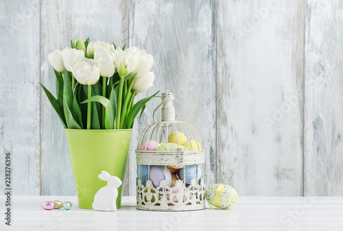 Leinwanddruck Bild Vintage bird cage full of colorful Easter eggs and spring flowers
