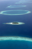 Blue and turqouise coral reef surrounding a small island, in the Maldives, aerial view, panorama from the air.