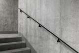 Concrete core with staircase and railing in a modern building, Elegant minimalist black steel railings